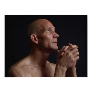 bald shirtless man clasps his hands in prayer, eyes pleading skyward